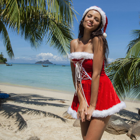 mrs: Beautiful woman in Mrs. Claus custume on tropical beach with palms, Christmas vacations concept Foto de archivo