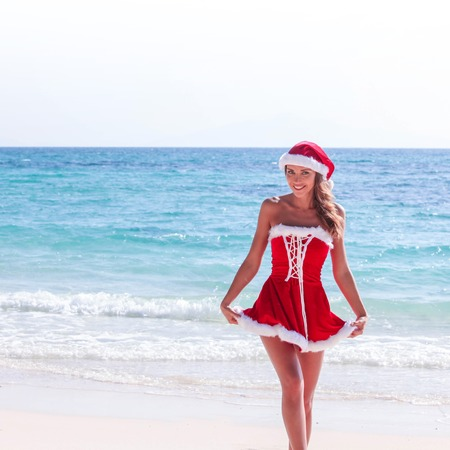 Beautiful woman in Mrs. Claus custume on tropical beach, Christmas vacations concept