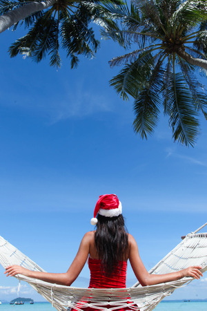 Woman in hammock on tropical beach celebrating Christmas
