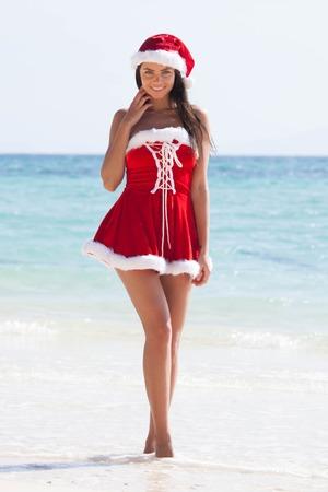 dona: Mujer hermosa en la señora Claus Custume en la playa tropical, el concepto de vacaciones de Navidad