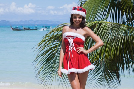 mrs santa claus: Beautiful woman in Mrs. Claus custume on tropical beach with palms, Christmas vacations concept Stock Photo