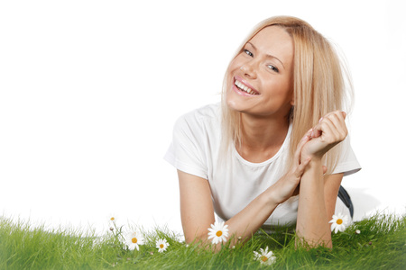 Happy young woman lying on grass with chamomile flowers, isolated on white background photo