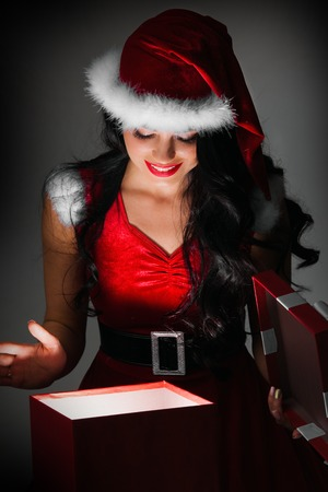 christmas costume: Woman in santa claus costume opening magic christmas gift