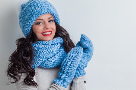 Smiling woman wearing blue winter hat, scarf and mittens Stock Photo