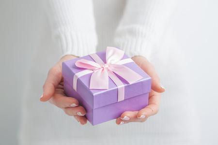 Frau mit kleinen lila Geschenk-Box in den Händen Standard-Bild - 66364735