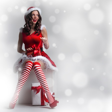 Beautiful pin-up Christmas woman in Santa Claus costume unpack gift Stock Photo