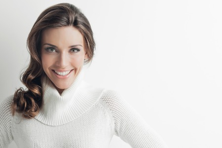 woman sweater: Studio portrait of beautiful long-haired woman in hot sweater on white background