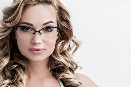 Glamorous green eyed blond woman with long curly hair wearing glasses looking directly at the camera on white