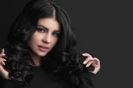 Beautiful woman holding her dark curly hair