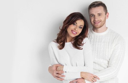 couples hug: Portrait of young smiling couple in white