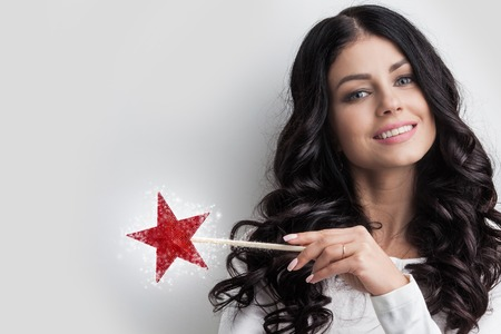 Woman with star shaped magic wand and sparks