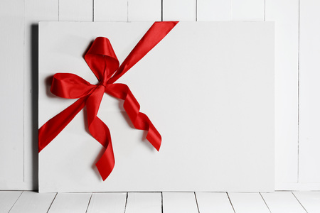 white ribbon: Decorative red ribbon and bow on a background of white painted rustic board with copyspace Stock Photo