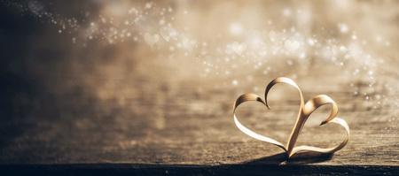 boda: Dos corazones mágicos de la cinta en el backround de madera, concepto del día de tarjeta del día de San Valentín Foto de archivo