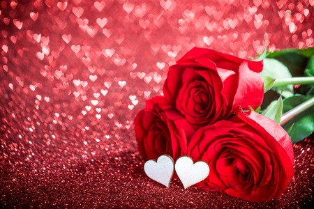 rosas rojas: Roses and hearts on red glowing bokeh hearts background for Valentines day Foto de archivo
