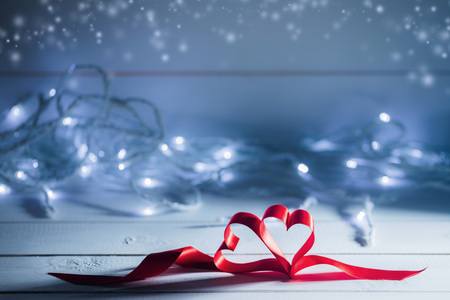 Valentines day ribbon hearts on glowing garland defocused bokeh lights background Stock Photo