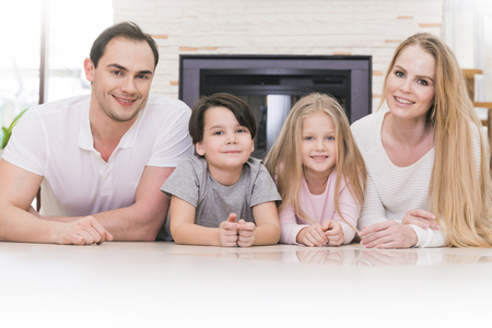 four people: Portrait of four people family with children at home over chimney background