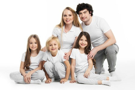 family isolated: Studio portrait of family in white clothes with three children isolated on white background