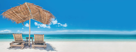 rest: Two bamboo chairs under straw umbrella on tropical beach