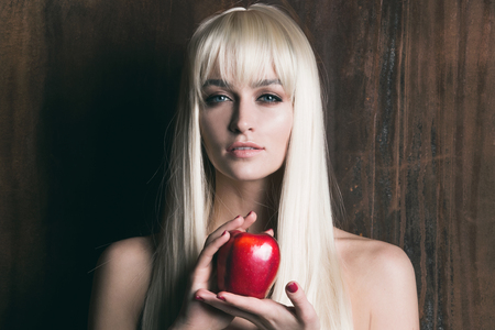 nude blonde girl: Young pretty blonde woman with long hair holding red apple on wooden background Stock Photo