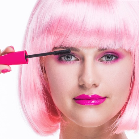 glamour hair: Portrait of girl with glamour make-up and pink hair using mascara isolated on white background