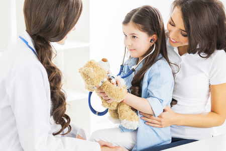 Mother and daughter at pediatrician office, girl examinate heart beat of teddy bear with stethoscope Standard-Bild