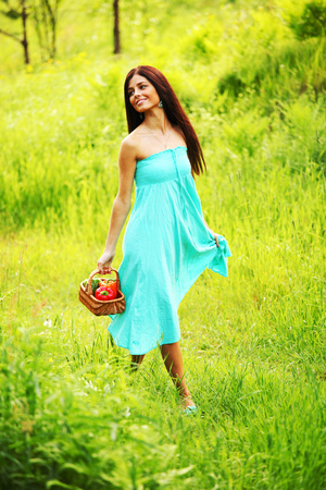 Beautiful young woman walking on summer grass field with basket of paprica photo