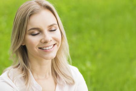 芝生の上の美しい若い女性は、目を閉じて笑って自然を楽しむ