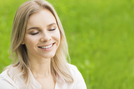 Eine schöne junge Frau auf Gras genießen die Natur lächelnd mit geschlossenen Augen