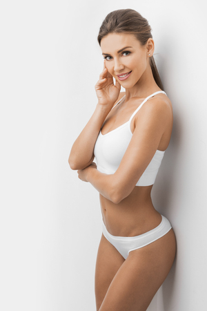 Fitness woman with a beautiful body in white cotton lingerie