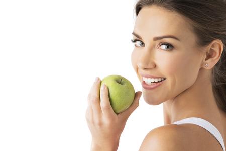 白い背景に分離された緑のリンゴを保持して健康な白い歯と美しい女性
