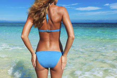 Back of young woman in bikini standing on tropical beach