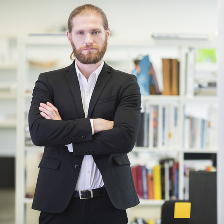 Portrait of hansome redhead bearded business man in office keeping arms crossed and looking at camera Stock Photo