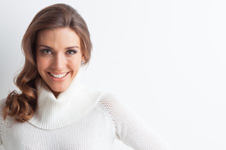 winter fashion: Studio portrait of beautiful long-haired woman in hot sweater on white background