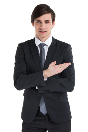 Portrait of young business man in black suit pointing on something with hand isolated on white background