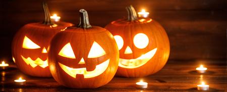 Halloween Kürbis Köpfe Jack O Laterne und Kerzen auf hölzernen Hintergrund Standard-Bild