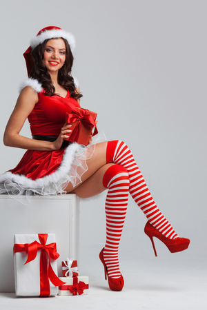 サンタの美しい少女ピンナップ ドレス クリスマス プレゼントを開ける 写真素材