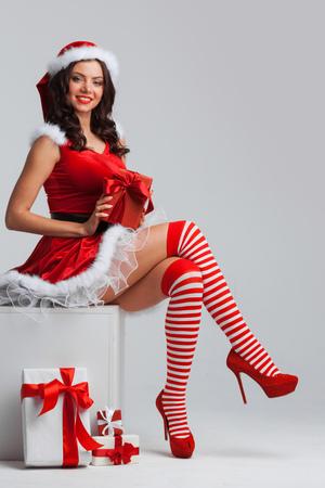 크리스마스 선물을 unwrapping 산타 드레스에서 아름 다운 젊은 핀 - 업 소녀