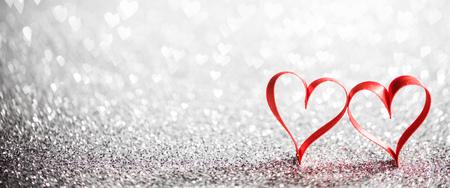Two ribbon hearts on glowing bokeh lights background Stockfoto