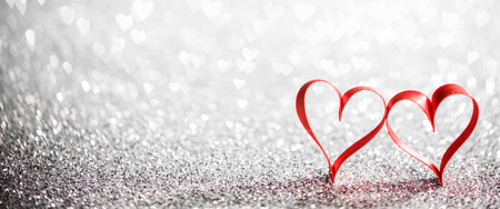 Two ribbon hearts on glowing bokeh lights background Stock Photo