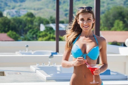 Portrait of girl with perfect body in bikini with cocktail near Jacuzzi at resort Stock Photo