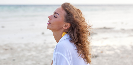 Attractive woman enjoy sea scent smelling wind with closed eyes on sea beach