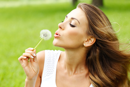 Young beautiful woman blows dandelion in the summer sunny park Stock Photo