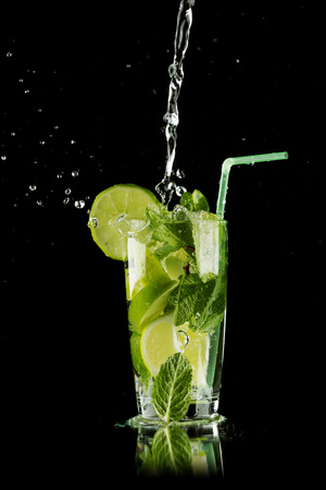 Pouring fresh mojito cocktail in glass isolated on black background