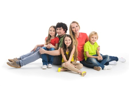 Happy smiling family of two parents and three children sitting on the floor studio isolated on white background Stock Photo
