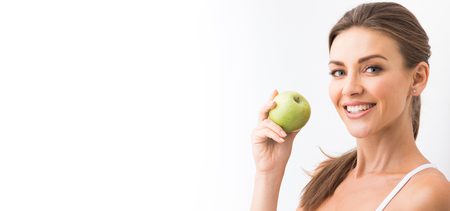 Beautiful smile, white strong teeth. Head and shoulders of young woman with snow-white toothy smile holding green apple, teethcare. Stock Photo
