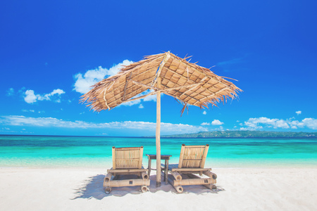Two chaise lounges and straw umbrella on tropical beach