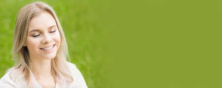 A beautiful young woman on grass enjoy nature smiling with closed eyes, green copy space, for text