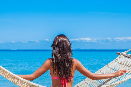 Young woman sitting in a hammock on a tropical beach and looking at sea Stock Photo