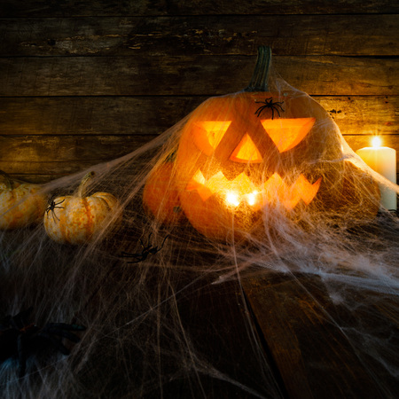 Jack O Lantern Halloween pumpkin , spiders on web and burning candles Stock Photo