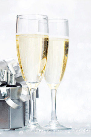 Glasses of champagne and silver gifts isolated on white